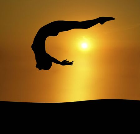 arching: silueta de mujer atr�s de buceo en la puesta de sol brillante de fondo