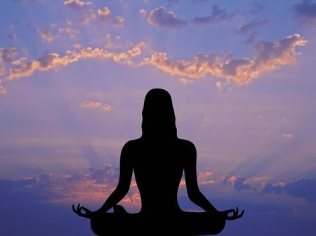 front silhouette of woman meditating under pink and purple sunrise