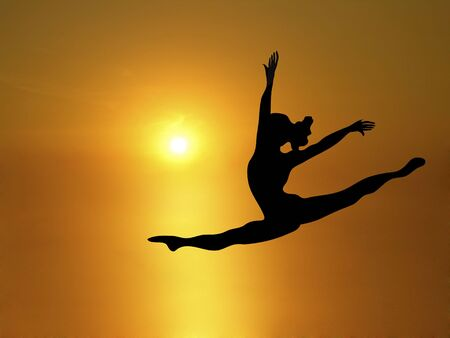 silhouette of woman dancing into brilliant yellow sunset Stock Photo