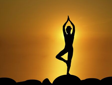 silhouette of woman in standing yoga pose with sunrise in the background Stock Photo