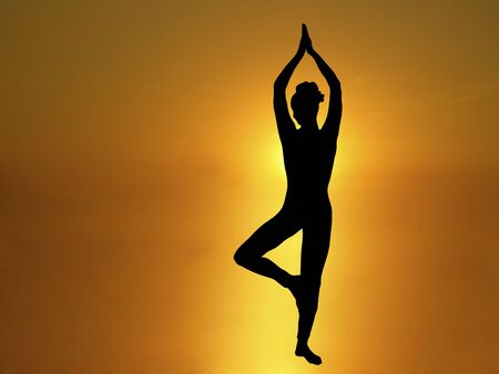 silhouette of woman doing yoga with  golden sunrise in background Stock Photo - 2527516