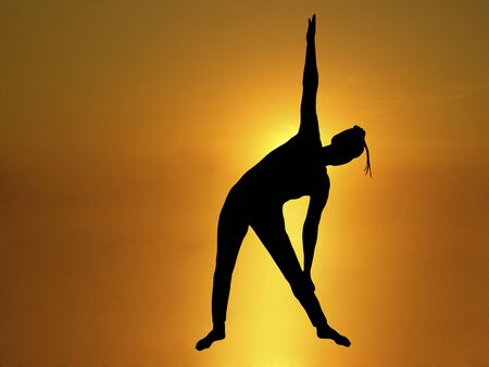 silhouette of woman doing yoga with  golden sunrise in background photo