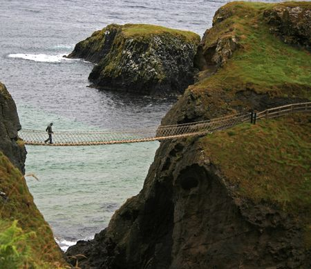 man crossing rope bridge in Ireland Stock Photo