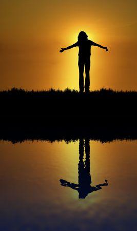 silhouet van de vrouw met open armen bij zonsondergang Stockfoto