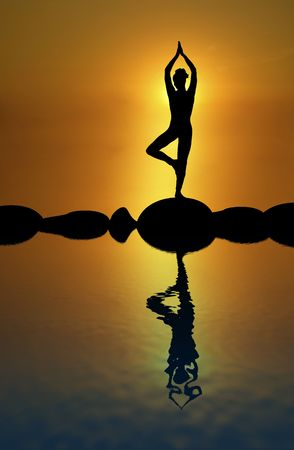 mind body soul: silhouette of woman in standing yoga pose with sunrise in the background Stock Photo