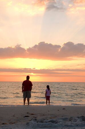 Father and Daughter enjoy beach sunset together