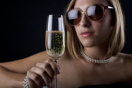 Young woman with champagne glass, sunglasses and jewelry photo