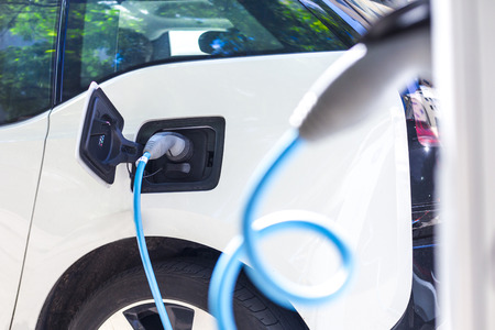 charged: Power supply for electric car charging. Electric car charging station. Close up of the power supply plugged into an electric car being charged. Stock Photo
