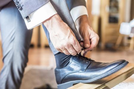 nahaufnahme: Bräutigam auf Hochzeit bindet sich die Schuhe, Detail
