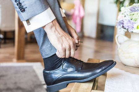 Bräutigam auf Hochzeit bindet sich die Schuhe, Detail
