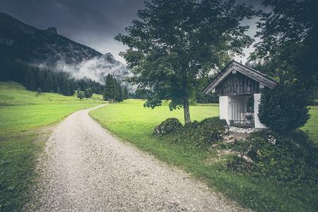 Wanderweg mit Wegkreuz und kleiner Kapelle in den Alpen Standard-Bild