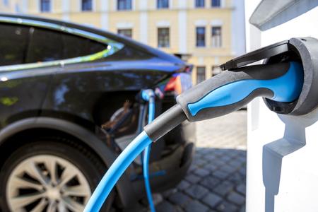 Schließen Sie das Netzteil, das in ein elektrisches Auto gesteckt wird, das aufgeladen wird Standard-Bild - 88469865