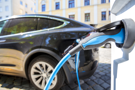 Close up of the power supply plugged into an electric car being charged