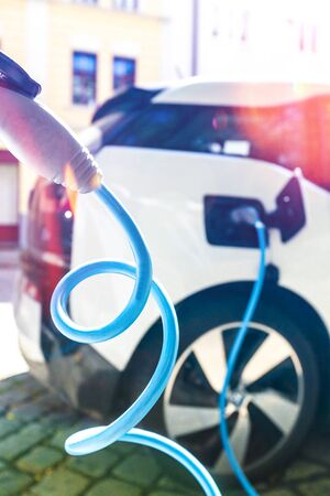 Power supply for electric car charging. Electric car charging station. Close up of the power supply plugged into an electric car being charged. Stock Photo