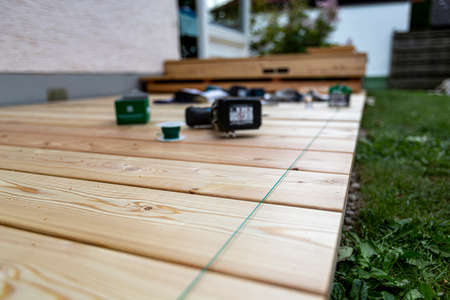 Building site - laying larch floorboards on a terrace. Installing of siberian larch flooring. Standard-Bild
