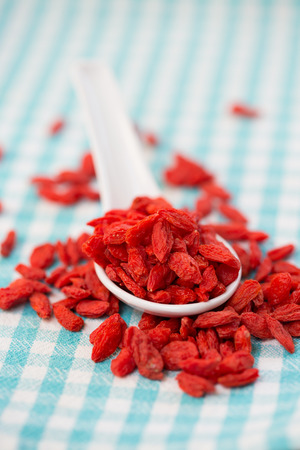 checked fabric: dried goji berries in white spoon on checked fabric Stock Photo