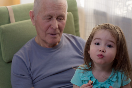 Cute little girl sitting with her grandfather