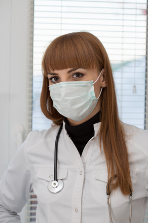 Female doctor with stethoscope wearing surgical mask Stock Photo
