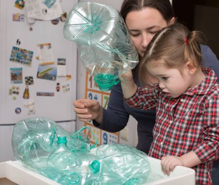 Little girl and her mother collecting plastic for recycling photo
