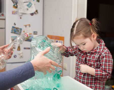 Little girl collecting plastic for recycling with her mother photo