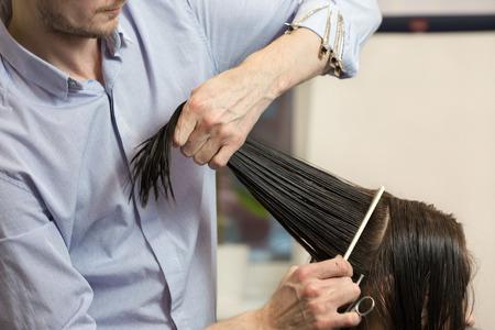 peluqueria: Peluquer�a haciendo un corte de pelo de una chica morena Foto de archivo