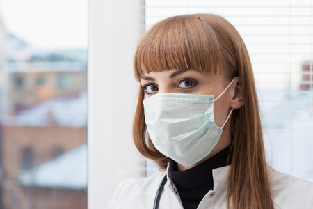 Beautiful female doctor wearing surgical mask Stock Photo