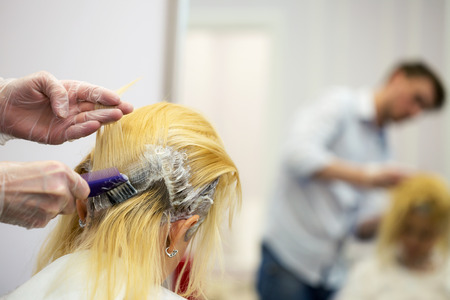 A hairdresser dyeing hair for a blonde girl