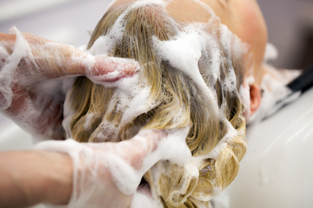 hairdressing: Hairdresser washing hair for a blonde girl in hair studio