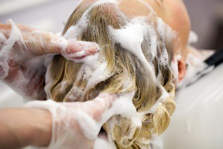 champú: Peluquería de lavar el cabello de una chica rubia en el estudio del cabello