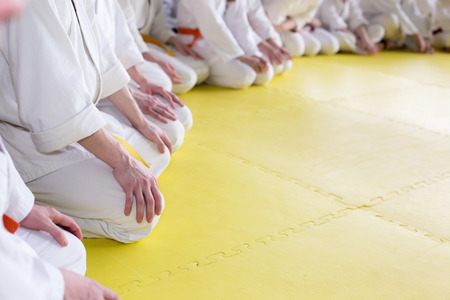 People in kimono sitting on tatami on martial arts training