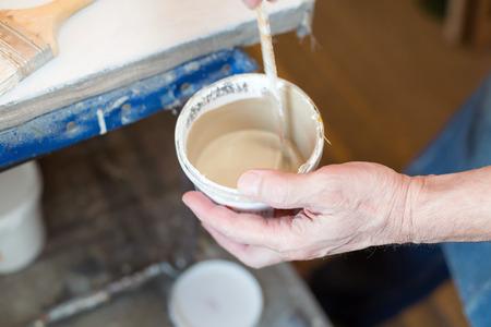 priming brush: An artist preparing primer for canvas