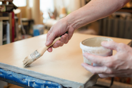priming brush: An artist priming canvas