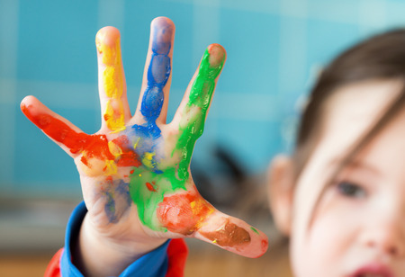 A little girl fingerpainting Stock Photo
