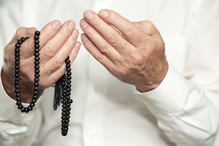 orando manos: Praying hands of an old man holding rosary beads