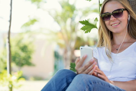 A beautiful blonde woman sitting in a park and surfing in the net with her smartphone