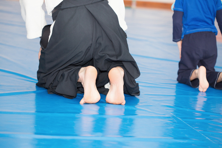 drop off: Aikido instructor sitting on tatami Stock Photo