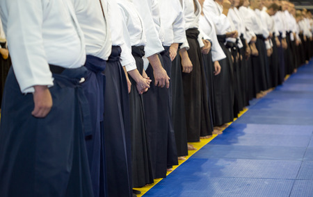 sensei: People in kimono and hakama standing in a long line on martial arts training seminar. Selective focus