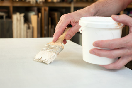 An artist priming canvas with brush. Selective focus Stock Photo