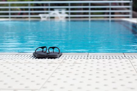 swimming shoes: Slippers near the swimming pool Stock Photo