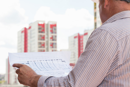 construction project: An engineer holding in hands blueprints on a background with buildings Stock Photo