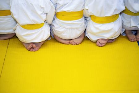 sensei: Group of children in kimono sitting on tatami on martial arts training seminar