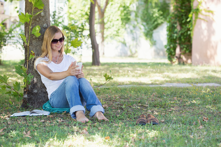 surfing the net: A beautiful blonde woman sitting in a park and surfing in the net with her smartphone