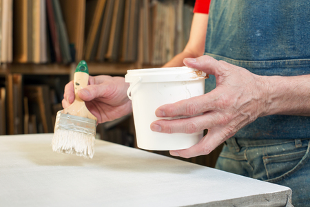 priming brush: An artist priming canvas