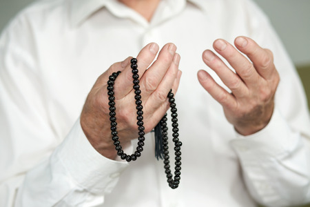 Praying hands of an old man holding rosary beads. Selective focus Stock Photo