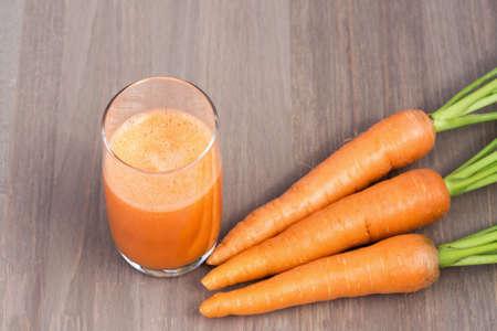zanahoria: Un vaso de licuado de zanahoria saludable con zanahoria sobre fondo de madera Foto de archivo