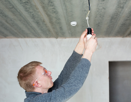 A man in safety glasses changing energy saving light bulbs Standard-Bild
