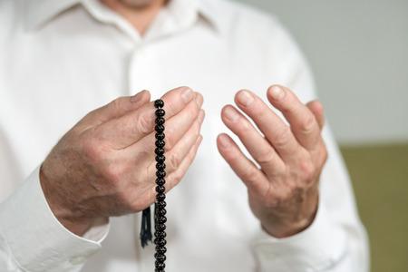 hombre orando: Orar manos de un hombre que sostiene viejas cuentas del rosario. Enfoque selectivo Foto de archivo