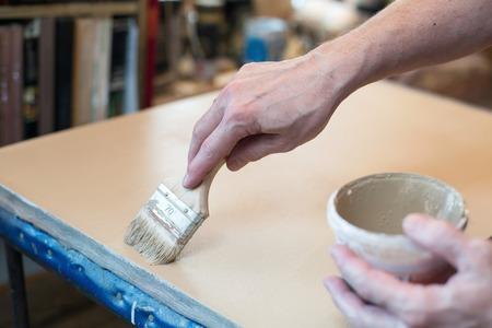 priming brush: An artist priming canvas for oil painting Stock Photo
