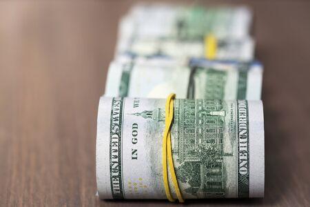 cash money: A rollos de billetes de cien dólares estadounidenses sobre una mesa de madera