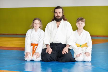 sensei: Two kids sitting on tatami with their Aikido sensei